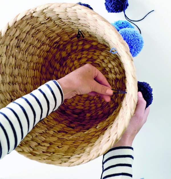Thread the pompom string through the basket. From Make & Do by Beci Orpin, via WeeBirdy.com.