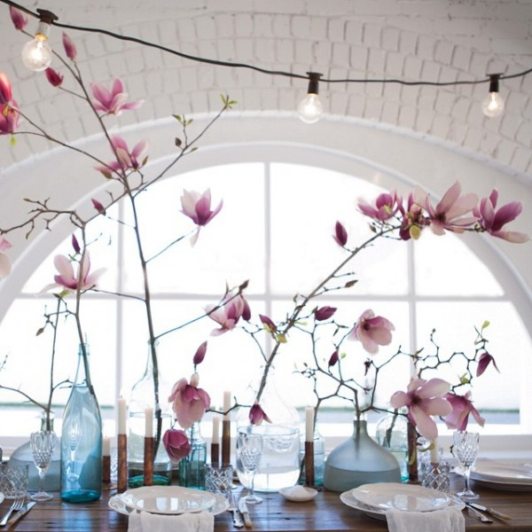 Magnolias and string lights combine for a pretty table setting, via The Lane.