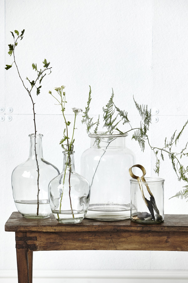 How to style a vignette inspired by by Danish brand House Doctor: glass jars and foliage.
