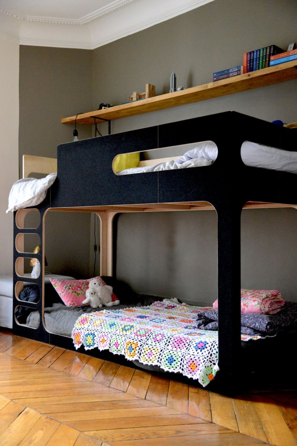 A matt black bunk bed makes smart choice for a shared space, with the girl's lower bed decorated with toys and a crochet quilt, while the boy's upper bunk is decorated with his favourite colours, via vanessapouzet.
