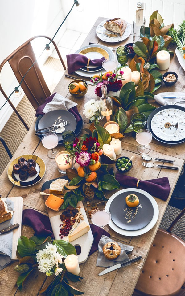 Persimmons and magnolia leaves make a colour match in heaven in this tabletop via Apartment 34.